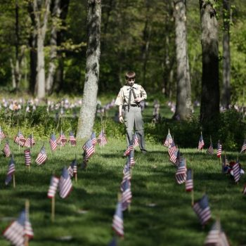 Volunteers place flags on Fort Custer National Cemetery graves