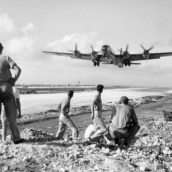 American soldiers watch a B-29 Superfortress heavy bomber take off from the island of Saipan in the Pacific Dec 1944 - Guadalcanal and HMAS Canberra Anniversary Tour